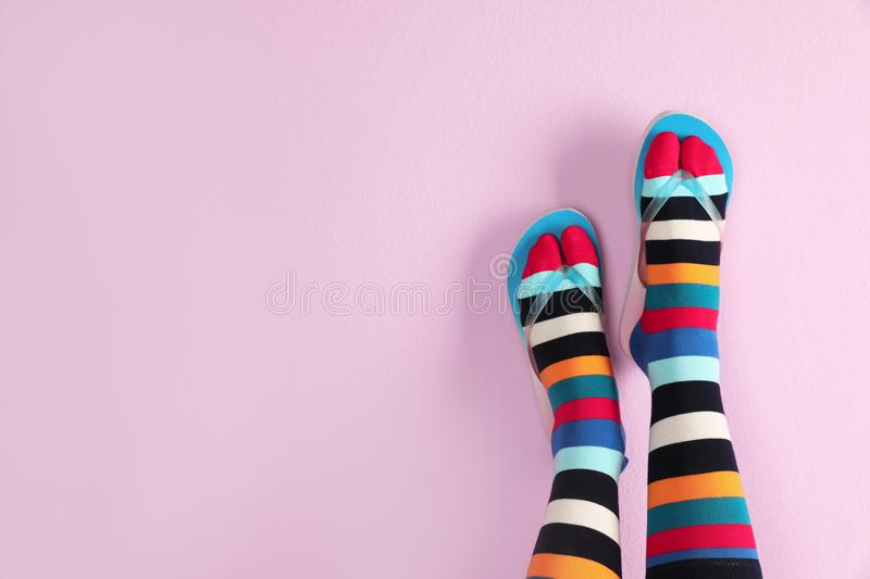 Woman wearing bright socks with flip-flops. And space for design on color background royalty free stock images