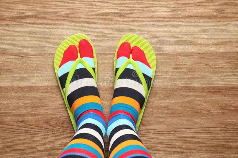 Woman wearing bright socks with flip-flops standing on floor, top view stock photos