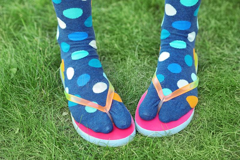 Woman wearing bright socks with flip-flops standing. On grass royalty free stock photos