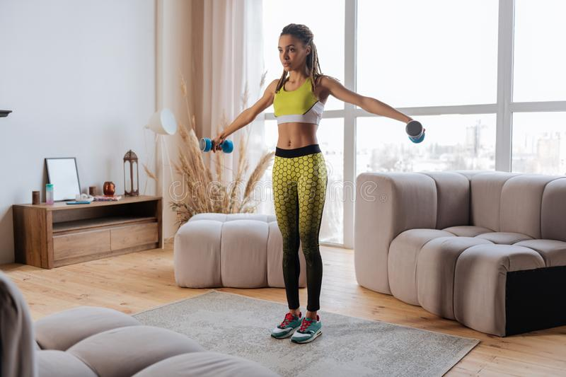Woman wearing bright yellow leggings doing exercises with barbells royalty free stock images