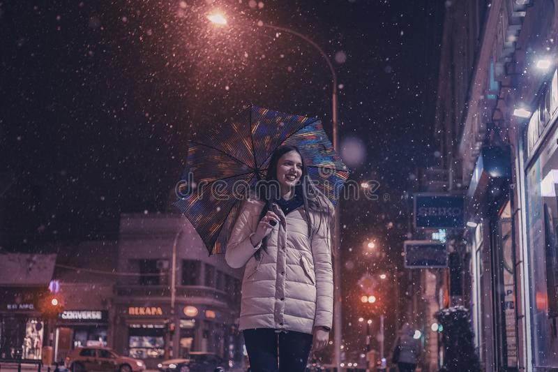 Woman Wearing Brown Bubble Jacket Holding Teal and Yellow Umbrella Near Building stock photography