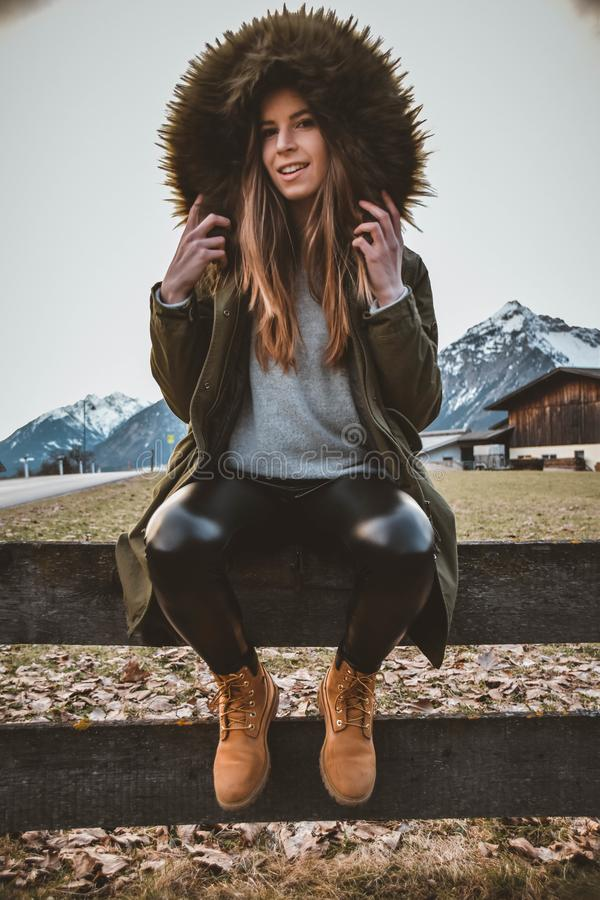 Woman Wearing Brown and Green Parka Sitting on Gray Wooden Fence at Daytime royalty free stock photos