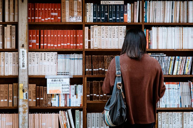 Woman Wearing Brown Shirt Carrying Black Leather Bag on Front of Library Books royalty free stock photo