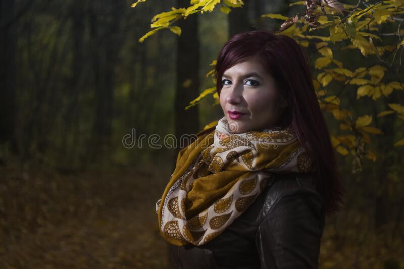 Woman Wearing Brown and White Scarf Surrounded by Trees at Daytime royalty free stock image
