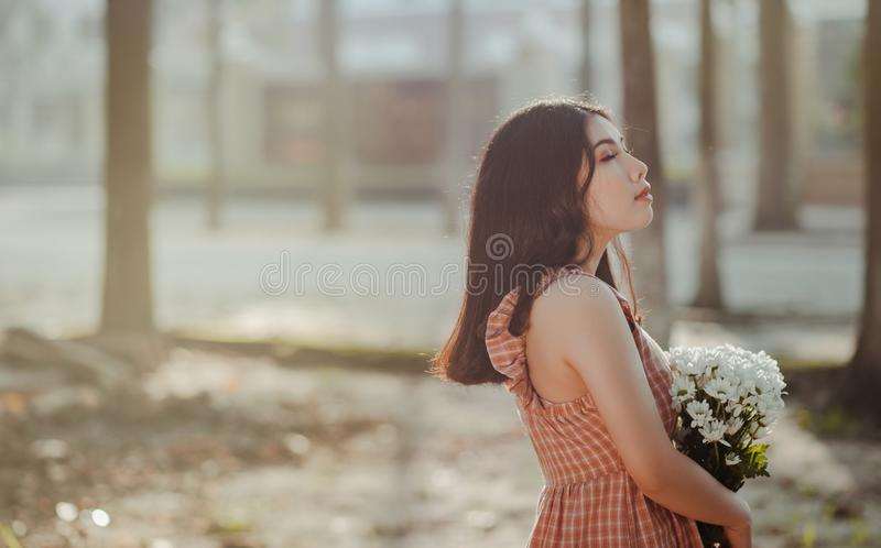 Woman Wearing Brown and White Scoop-neck Sleeveless Dress Holding a Bouquette of White Petaled Flower royalty free stock photo
