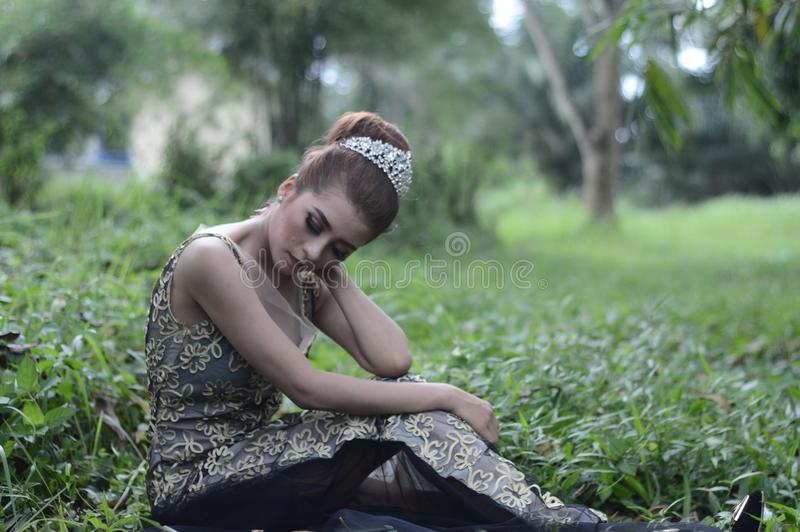 Woman Wearing Brown and White Sleeveless Floral Embroidered Dress Sitting on Green Grass Field royalty free stock image