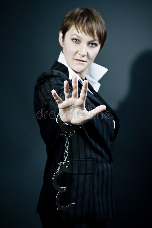 Woman gives stop signal by hand with handcuffs on royalty free stock image