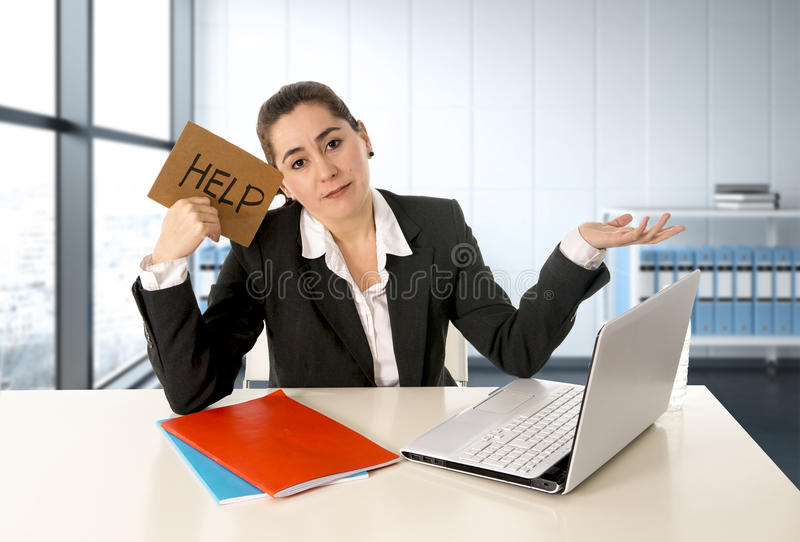 Woman wearing a business suit working on her laptop holding a help sign sitting at modern office royalty free stock photography