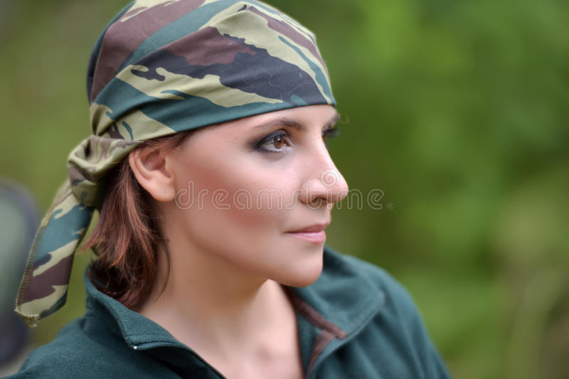 Woman wearing camouflage bandana against the backdrop of UAZ. Woman wearing camouflage bandana and a green fleece jacket stock image