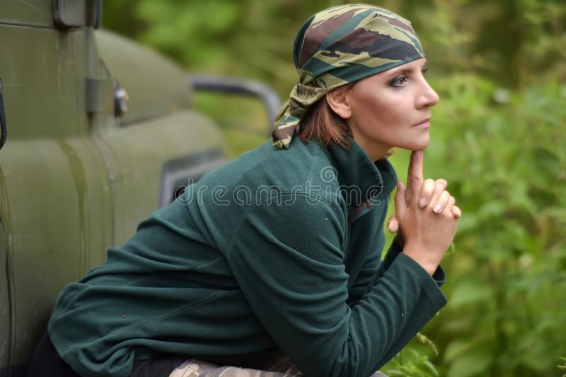Woman wearing camouflage bandana. Against the backdrop of UAZ. Fashion, brave stock photography