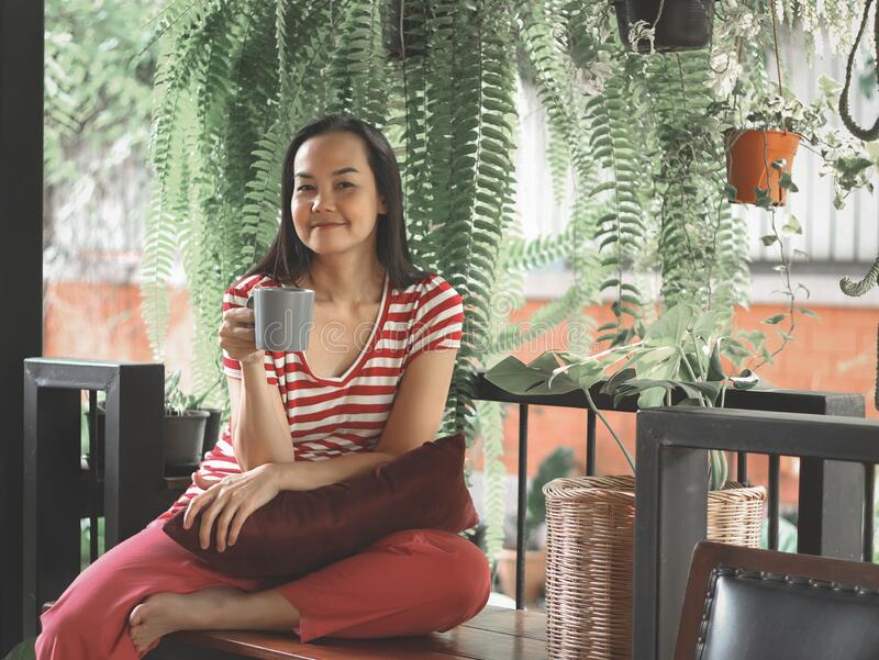 Woman wearing casual red stripe t-shirt sitting on bench in balcony garden , holding coffee cup smile and looking at camera.self. Asian woman wearing casual red royalty free stock photography