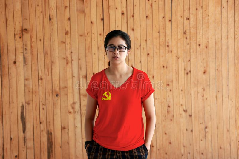 Woman wearing Chinese Communist Party flag color shirt and standing with two hands in pant pockets on the wooden wall background royalty free stock photos