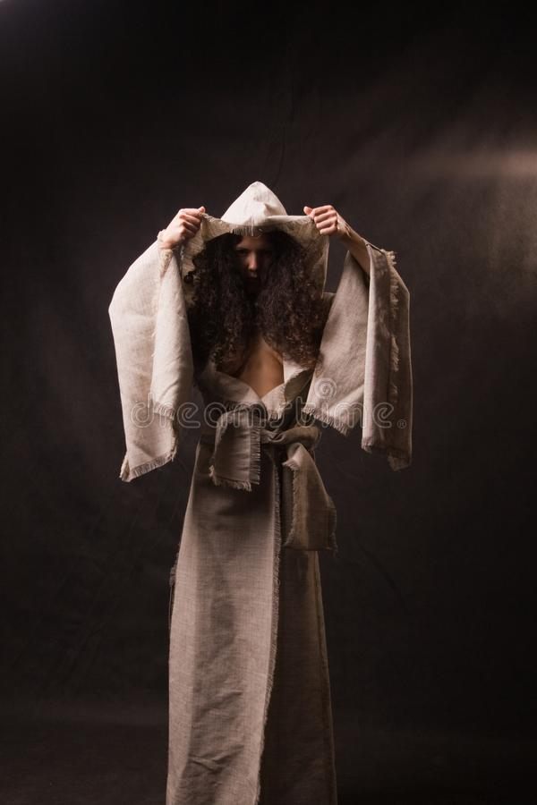 Woman wearing cloak. Woman wearing a natural fabric cloak or cape royalty free stock image