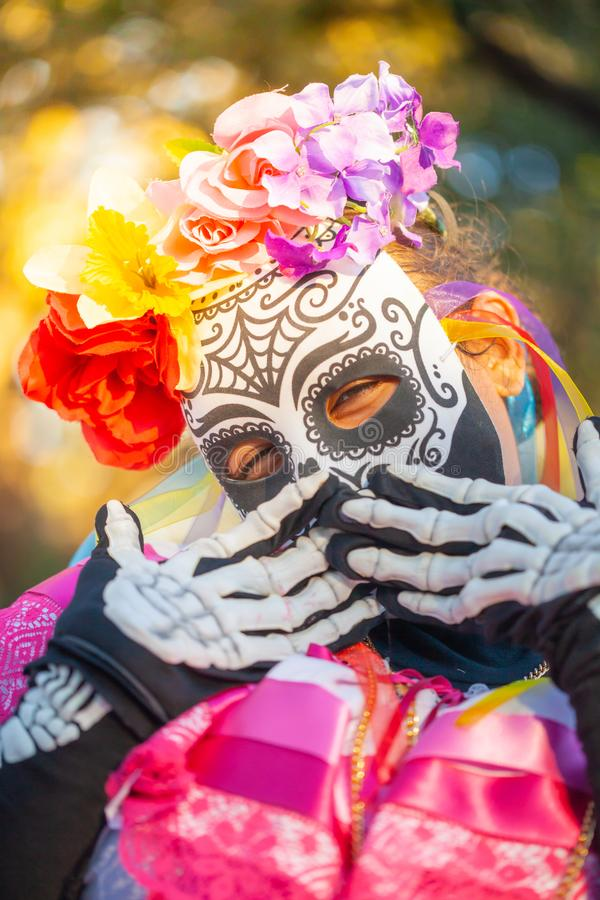 Woman wearing colorful skull mask and paper flowers for Dia de Los Muertos/Day of the Dead.  stock photo