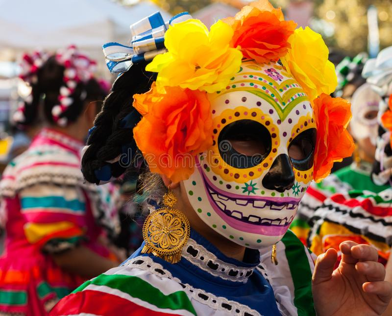 Woman wearing colorful skull mask and paper flowers for Dia de Los Muertos/Day of the Dead stock photo