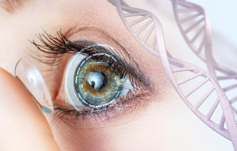 Woman wearing contact lens among DNA stems. Woman with green eye wearing contact lens among DNA stems royalty free stock images