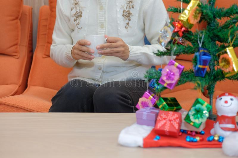 Woman holding coffee cup with gift box christmas tee. xmas new y. Woman wearing cream cardigan holding coffee cup with gift box christmas tee. xmas new year stock images
