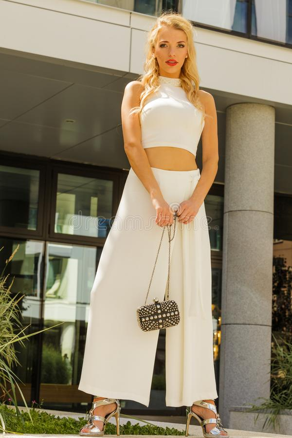 Woman wearing crop top and culottes. Fashion model woman wearing white outfit with crop top and wide trousers culottes stock images
