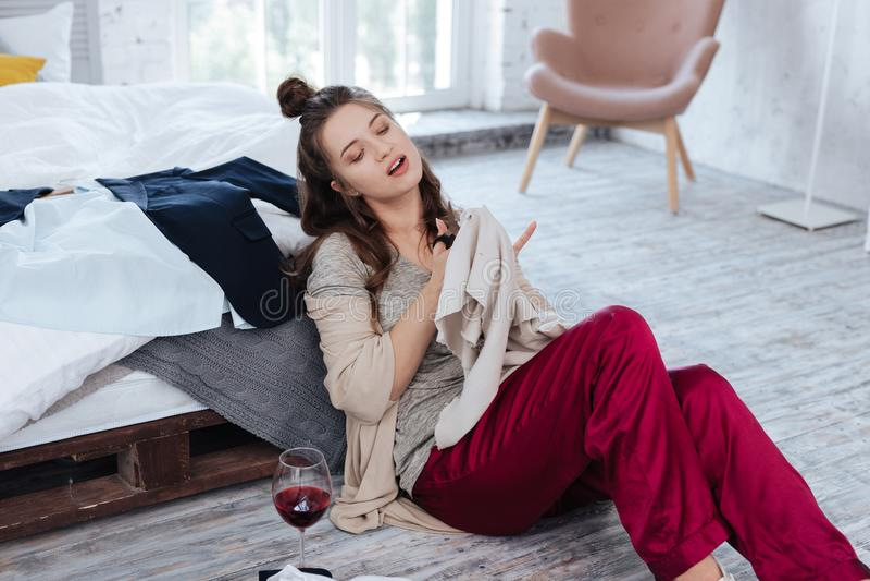 Woman wearing dark-red pajama trousers cutting sweater with scissors. Pajama scissors. Dark-haired crazy woman wearing dark-red pajama trousers cutting sweater royalty free stock image