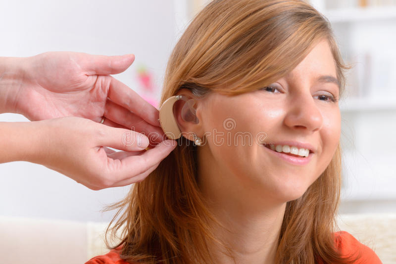 Woman wearing deaf aid. Putting on a deaf aid stock photography