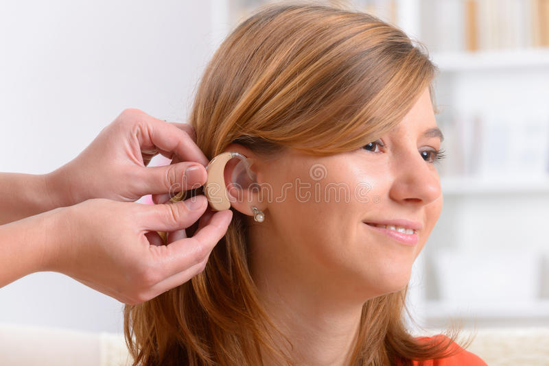 Woman wearing deaf aid. Putting on a deaf aid stock image