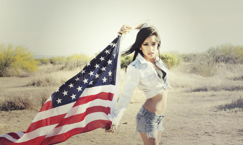 Woman wearing denim shirt holding American flag. Beautiful young woman wearing denim shirt holding American flag in the open desert. Image contains scratches and stock images