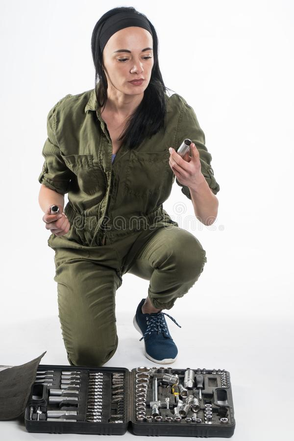 A woman wearing a DIY tool belt full of a variety of useful tools on a white background. Construction woman royalty free stock photography