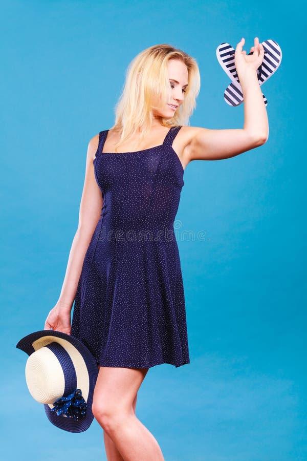 Woman wearing dress holding sun hat an flip flops stock image