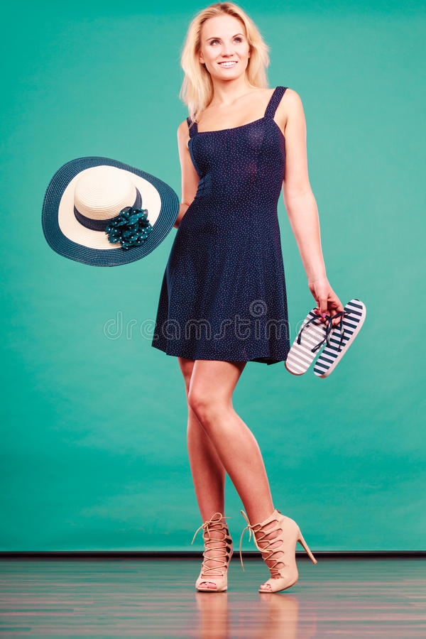 Woman wearing dress holding sun hat an flip flops. Summer trendy fashionable outfit ideas concept. Woman wearing short navy dress holding sun hat and flip flops royalty free stock photography