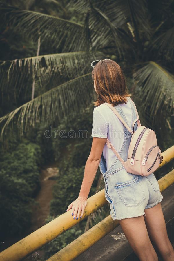 Woman Wearing Dungaree Shorts Stands Near a Yellow Metal Rail Overlook a River Belo With Coconut Trees at Daytime royalty free stock images