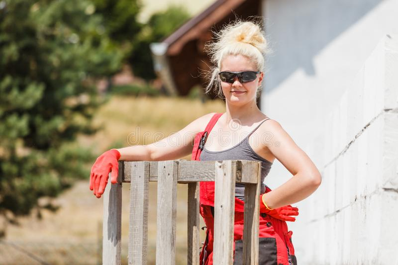 Woman in dungarees working on construction site stock photos