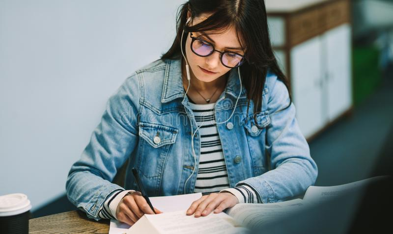 Woman wearing earphones writing notes from reference book at college library. Female student studying at university campus royalty free stock photos
