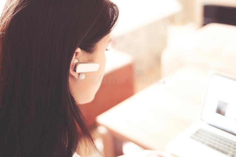 Woman Wearing Earpiece Using White Laptop Computer stock image
