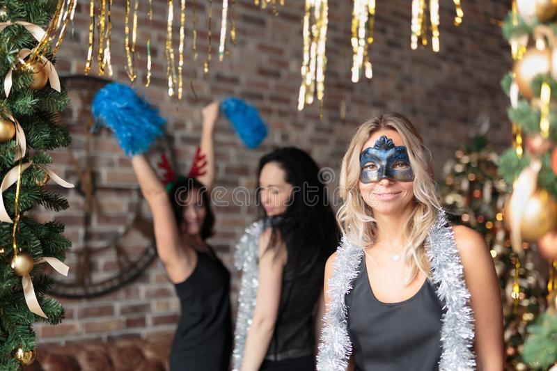 Woman wearing elegant black dress with mask having fun at New Year`s party stock photo