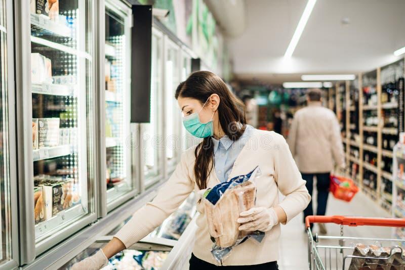 Woman wearing face mask buying in supermarket.Panic shopping during Coronavirus covid-19 pandemic.Budget buying at a supply store. Buying freezer smart royalty free stock images