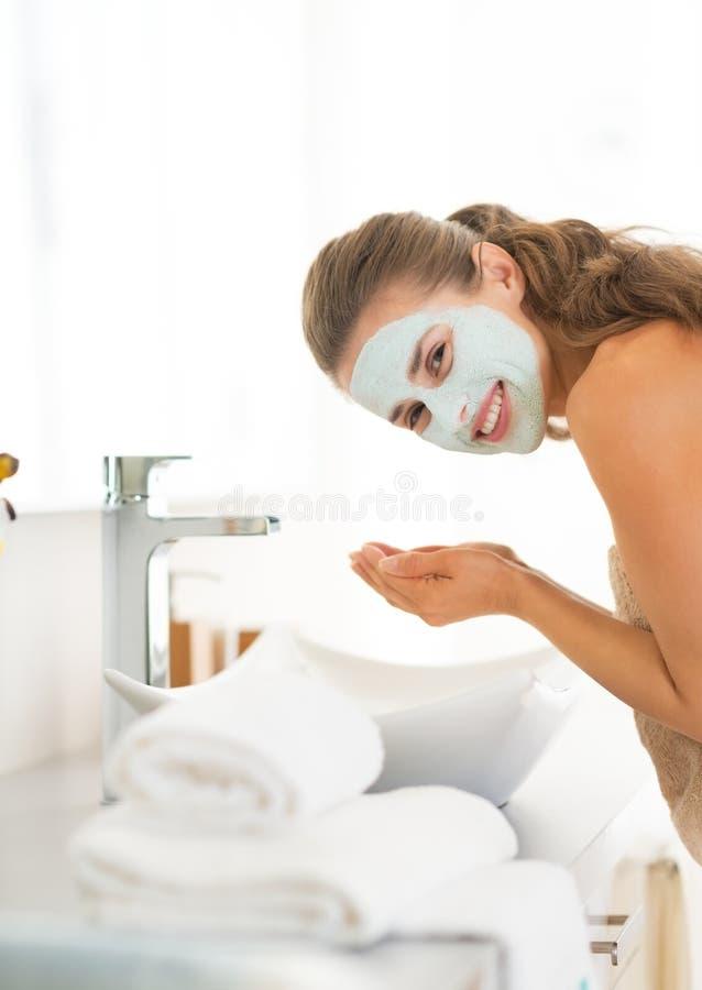 Woman wearing facial cosmetic mask washing face. Young woman wearing facial cosmetic mask washing face royalty free stock photos