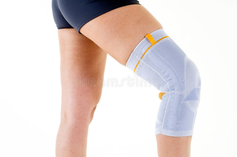 Woman Wearing Flexible Knee Brace in White Studio. Close Up of Woman Wearing Flexible Elastic Supportive Orthopedic Brace on Bent Knee in Studio with White royalty free stock photo