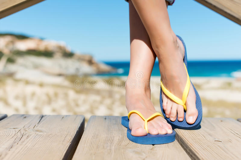 Woman Wearing Flip-Flops While Standing On Board Walk. Low section of woman wearing slippers while standing on board walk stock photography