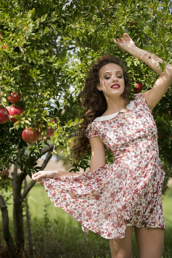 Woman wearing floral long dress against pomegranate trees. Young woman wearing floral long dress standing against pomegranate trees, the model look away having stock images