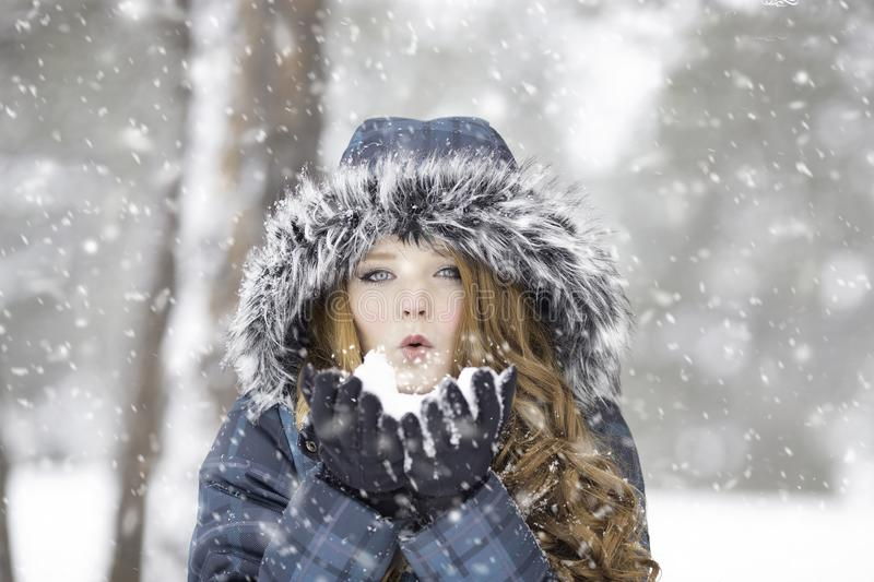 Woman wearing fur hood in a snow storm royalty free stock photography