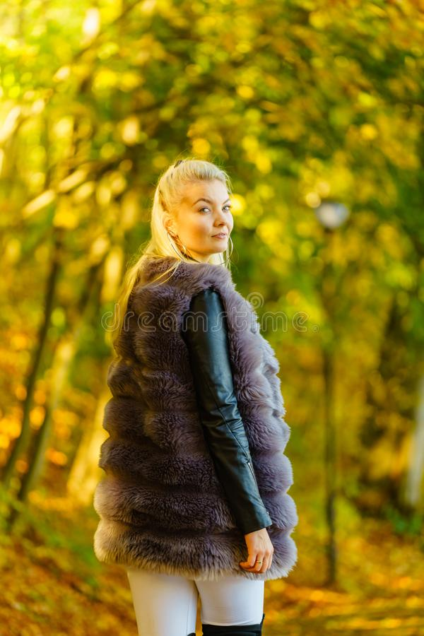 Woman wearing fur long vest during autumn stock image