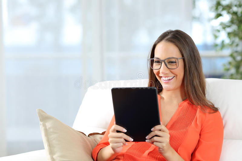 Woman wearing glasses reading a tablet royalty free stock photos