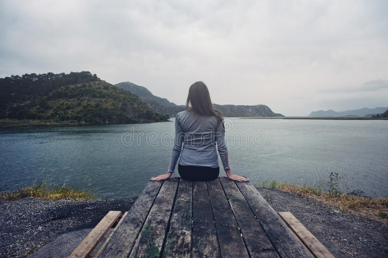 Woman Wearing Gray Long-sleeved Shirt and Black Black Bottoms Outfit Sitting on Gray Wooden Picnic Table Facing Towards Calm Body royalty free stock photo