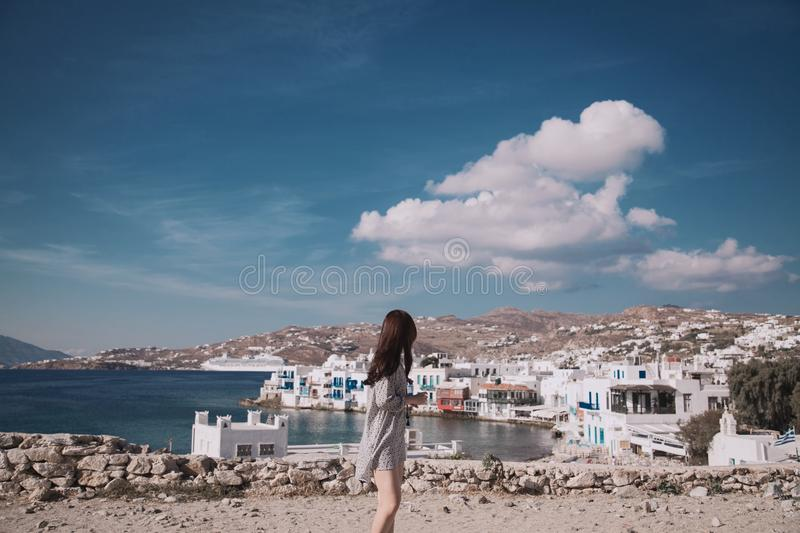 Woman Wearing Gray Shirt Standing in Front White Houses Beside Body of Water royalty free stock image