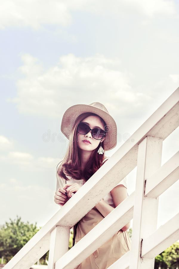 Woman Wearing Gray Sun Hat in Front of White Fence royalty free stock photos
