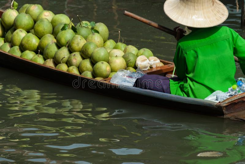 Floating market scene in Thailand. A woman wearing green floating her boat with produce at a Thai floating market royalty free stock photos