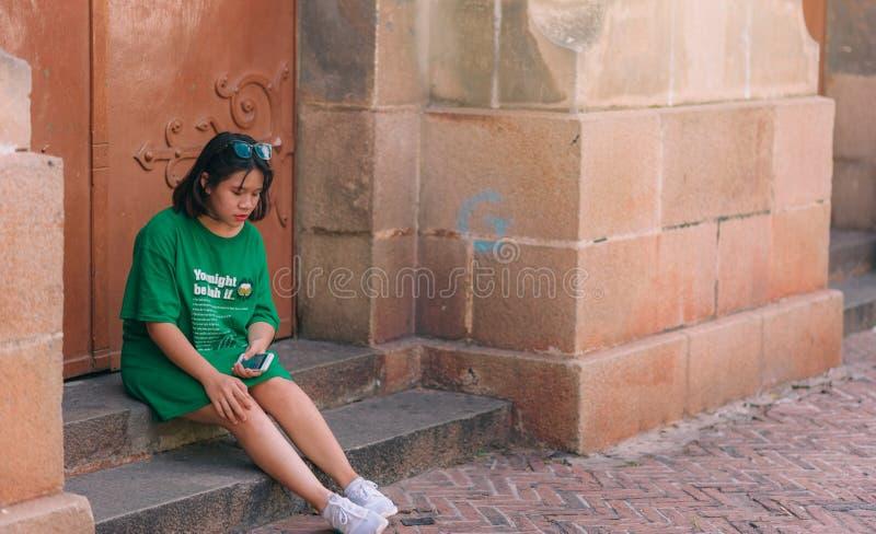 Woman Wearing Green Shirt Sitting Near Brown Gate Holding Smartphone royalty free stock photo