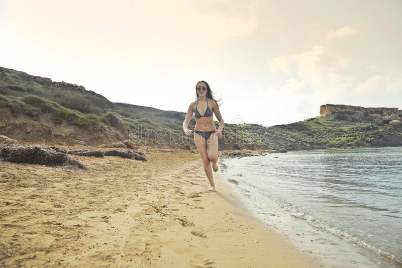 Woman Wearing Grey Bikini Running On White Sand Seashore stock photos