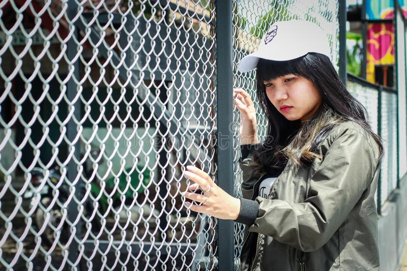 Woman Wearing Grey Bomber Jacket Leaning Near Grey Wire Fence royalty free stock photography