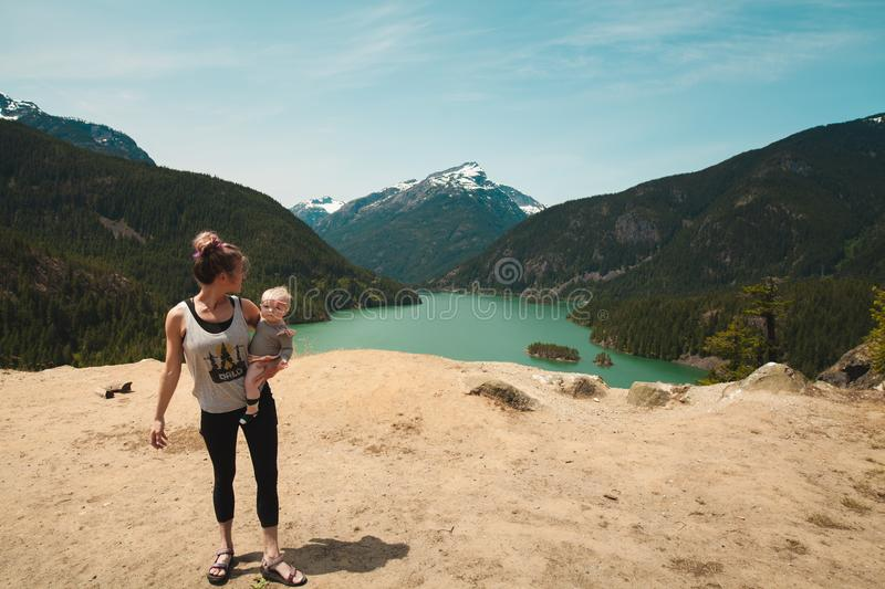 Woman Wearing Grey Tank Top Carrying Baby in Distant of Lake Between Mountains stock image